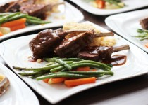 Rosa gebratenes Lammkarree an einer Knoblauch-Minz-Jus mit glasierten Karotten, weißem Spargel und grünen Bohnen auf Couscous
